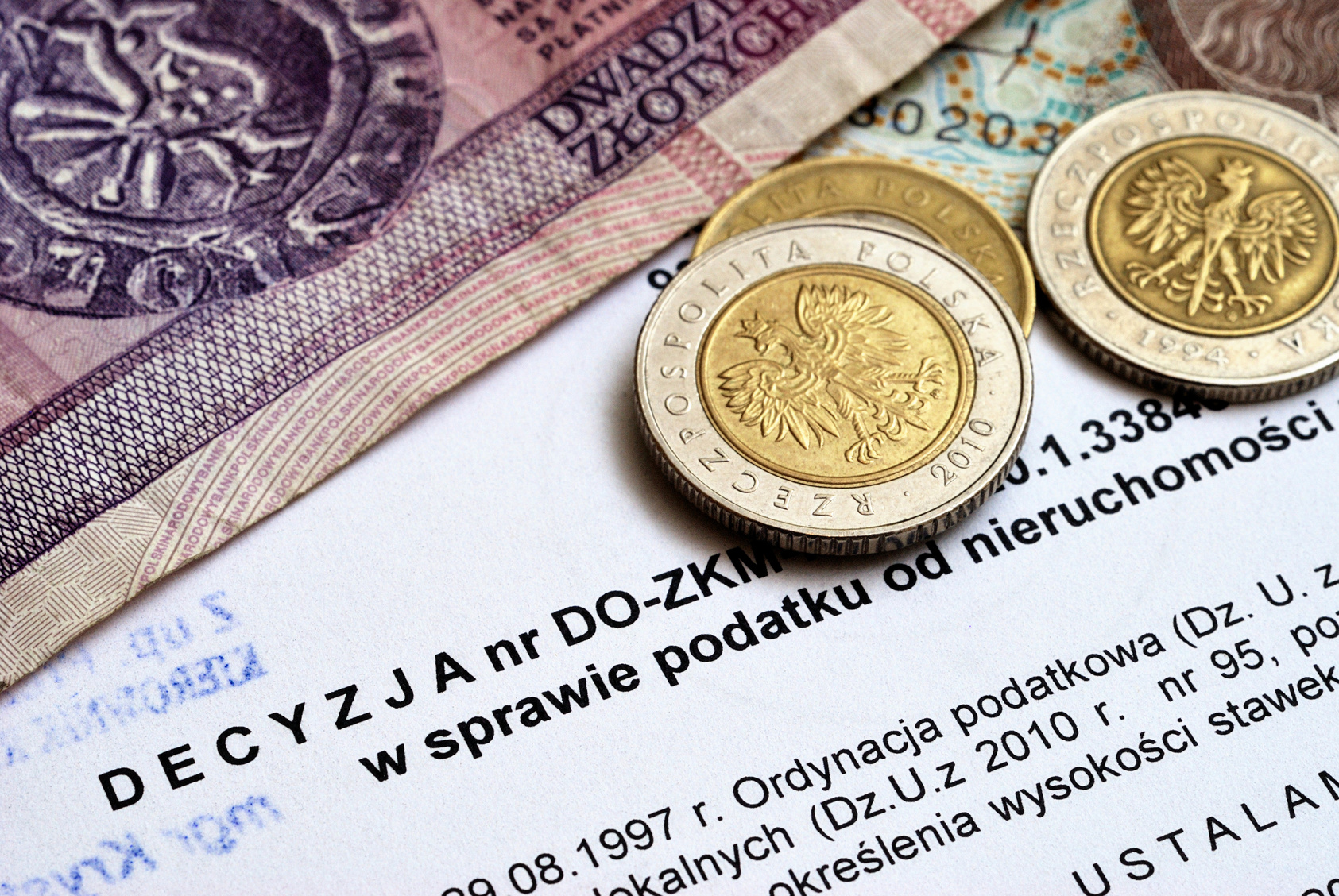 Dokument z decyzją podatkową. Na nim leżą monety i banknoty