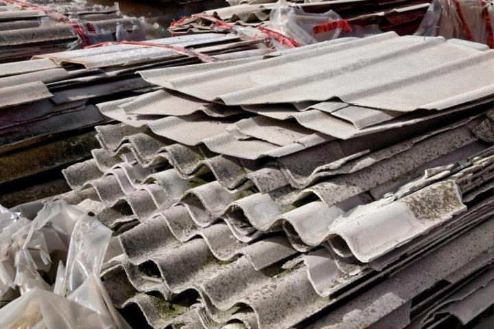 Stos zdjętych z dachu domu płyt azbestowych