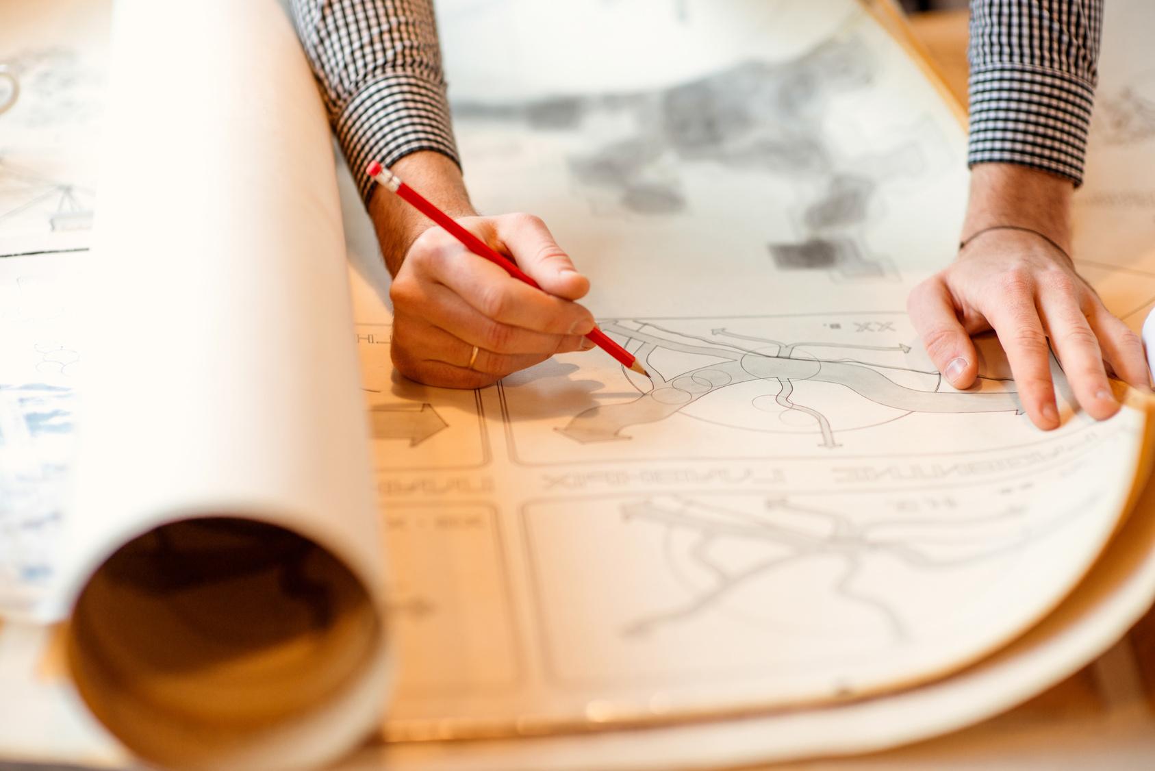 Rzowiniętaa mapa, nad nią pochylony mężczyzna, któy trzyma czerwony ołówek w ręku.