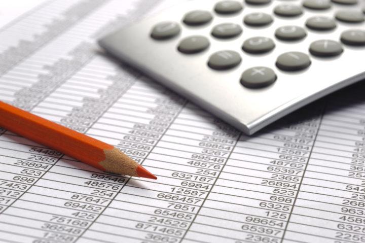 Kartka z tabelami liczbowymi, a na niej kalkulator i czerwona kredka