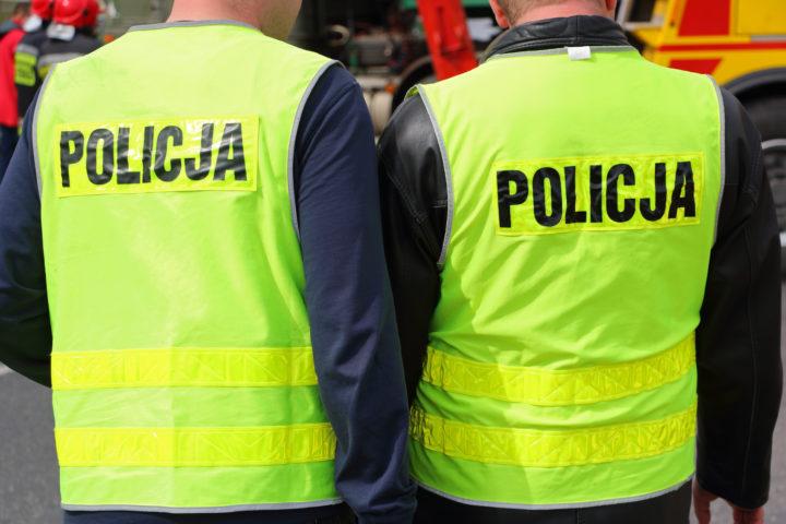 Policjanci od tyłu w odblaskowych kamizelkach z napisem policja