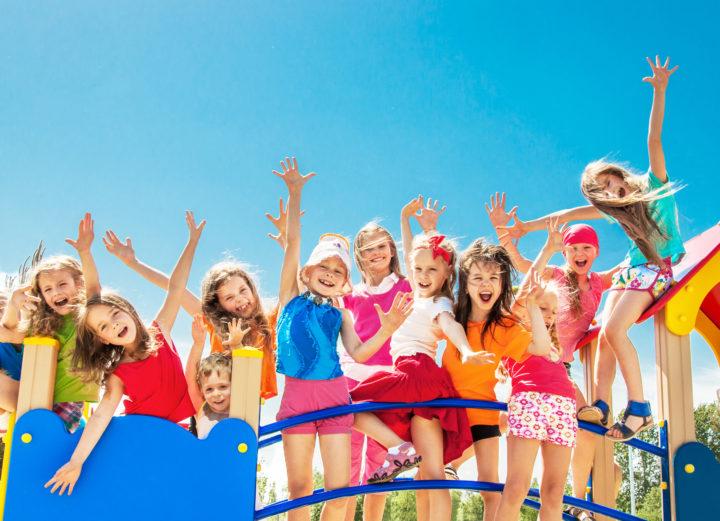 Grupa ubranych na kolorwo dzieci stoi na niebieskim mostku