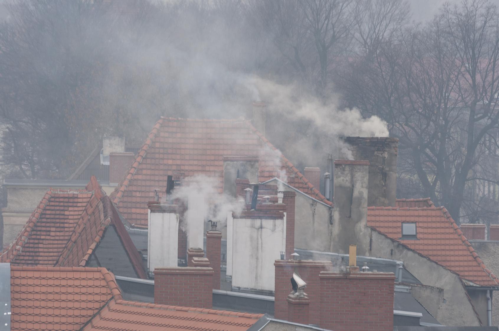 Dym lecący z kominów. Czerwone dachy domów