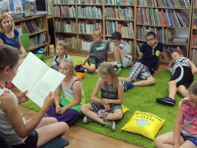 Dzieci czytają książkę na dywanie