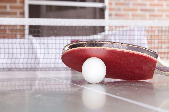 Czerwona paletka do tenisa stołowego leży na białej piłeczce