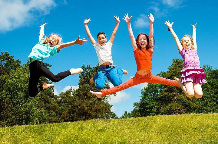 Czworo roześmianych dzieci uchwyconych podcza skoku