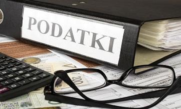 Biurko na którym leży czarny segregator z napisem Podatki, czarne okulary, kalkulator, pit i pieniądze