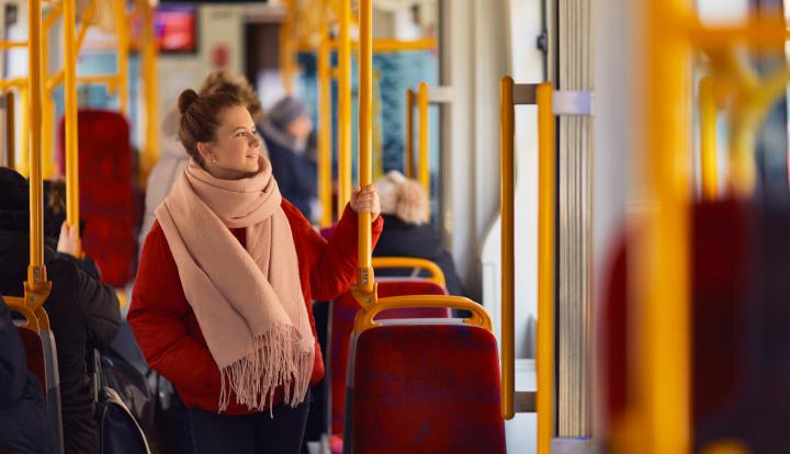 Kobieta w czerownej kurtce i brązowym szalu w środku autobusuKobieta w czerwonej kurtce i brązowym szalu w środku autobusu miejskiegomiejskiego