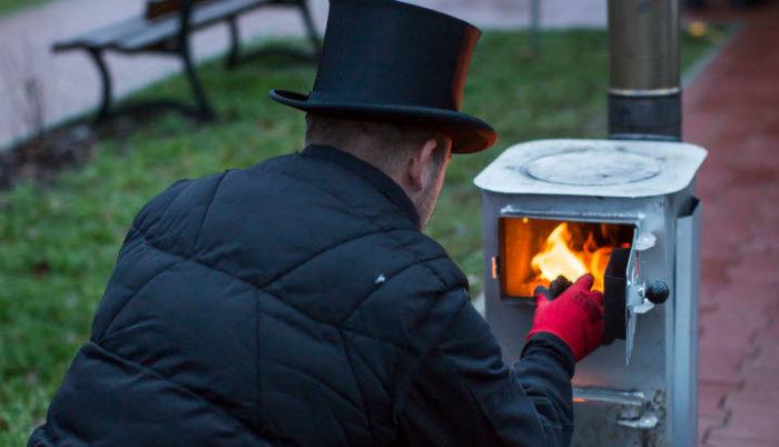 Kominiarz ubrany na czarn, od tyłu, rozpala ogień w kominku - kozie