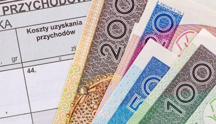 Banknoty 100, 50, 20 i 200 złotowe w tle formularz PIT