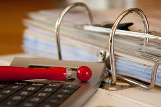 Segregator z dokumentami po prawej. Po lewej kalkulator, a na nim czerwony długopis