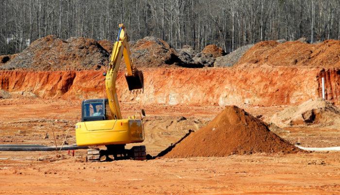 Budowa drogi. Żółta koparka przesypuje hałdy ziemi