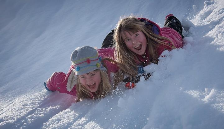 Dwie dziewczynki zjeżdżają na brzuchu po górce przysypanej śniegiem