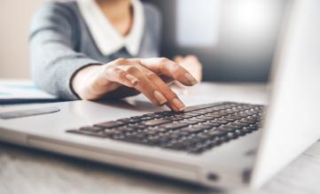 Szary, otworzony laptop. Nad czarną klawiaturą unosi się kobieca ręka