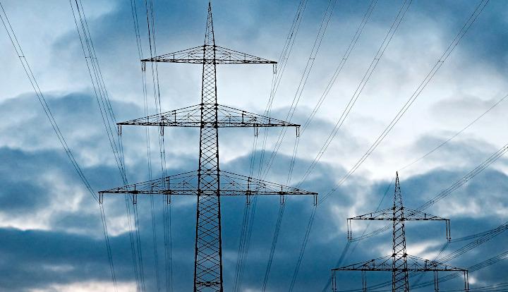 Linia energetyczna, wysokie słupy na tle niebieskiego nieba