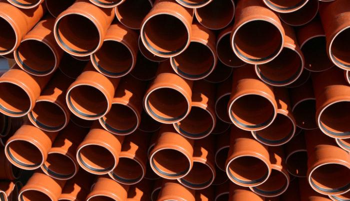Plastikowe rury w kolorze brązowym ułożone jedna na drugiej