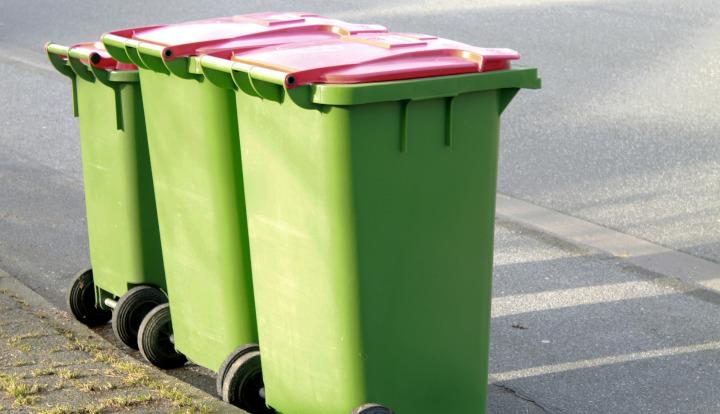 Trzy pojemniki na śmieci stojące przy krawężniku w kolorze zielonym z czerwoną klapą