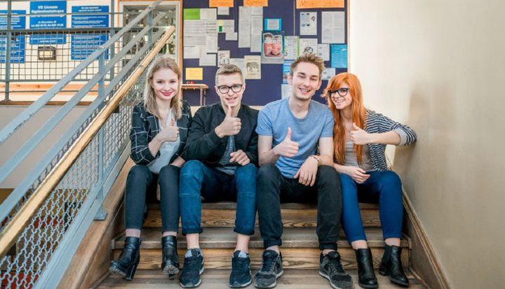 Czwórka młodych ludzi siedzi na szkolnych schodach. Wszyscy mają kciuki uniesione do góry.