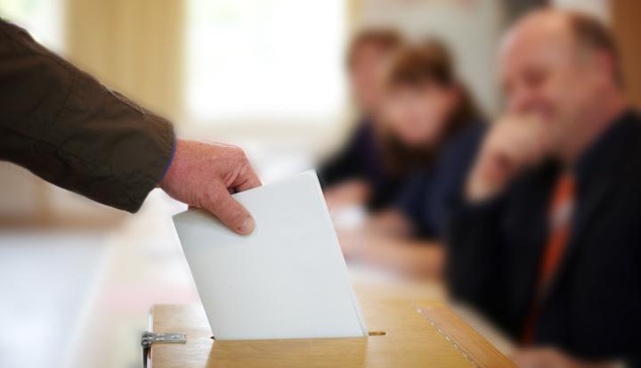 Wybory. Widać męską rękę, która wrzuca kartę do urny na głosy