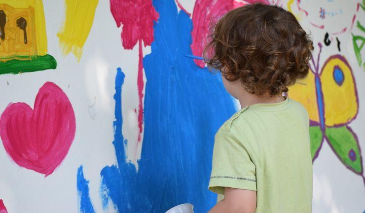 Dziecko odwrócne tyłem maluje na ścianie niebieską farbą