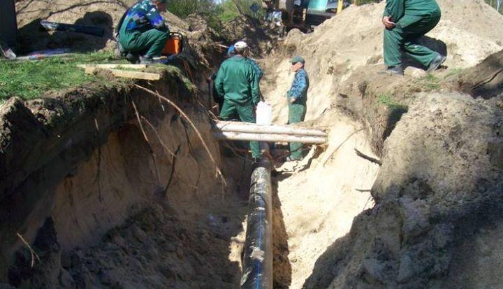 Głęboki rów, na dnie ułożone rury kanalizacyjne. W tle stoją robotnicy