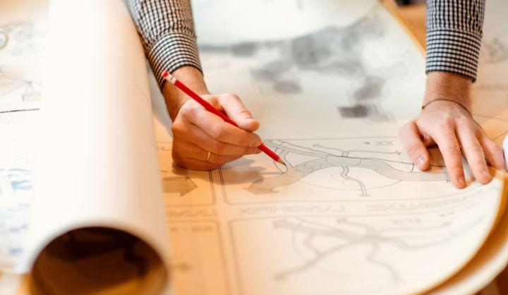 Ręka trzymające czerwony ołówek kreśli coś na mapach