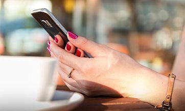 Czarny telefon komórkowy trzymany przez kobiece dłonie z czerwonymi paznokciami
