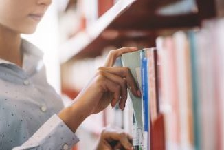 Półka z książkami. Kobieca ręka wyciąga książkę