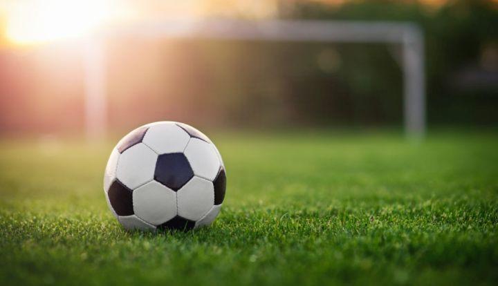 Piłka nożna biało-czarna na zielonej trawie. W tle bramka