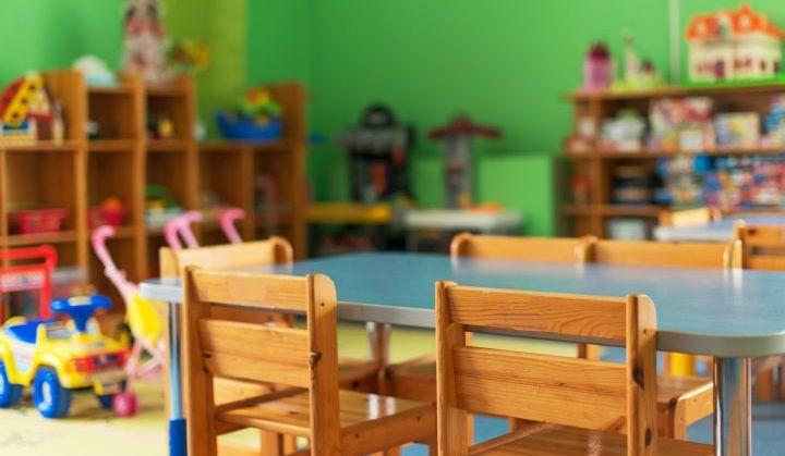 Sala przedszkolna. Na pierwszym planie stolik z krzesełami. W tle pułki z kolorowymi zabawkami