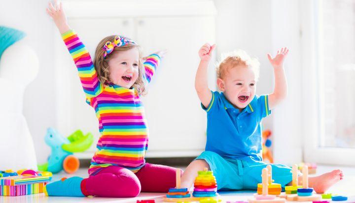 Dwoje dzieci z podniesionymi w górę rączkami cieszy się z zabawy