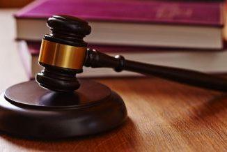 Drewniany młotek na podkładce. Młotka używa sędzia podczas rozprawy