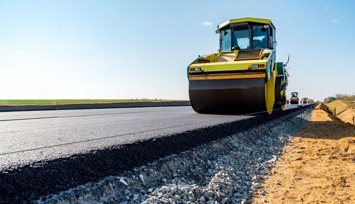 Żółty walce drogowy wyrównuję dopiero co wylany na drogę czarny asfalt