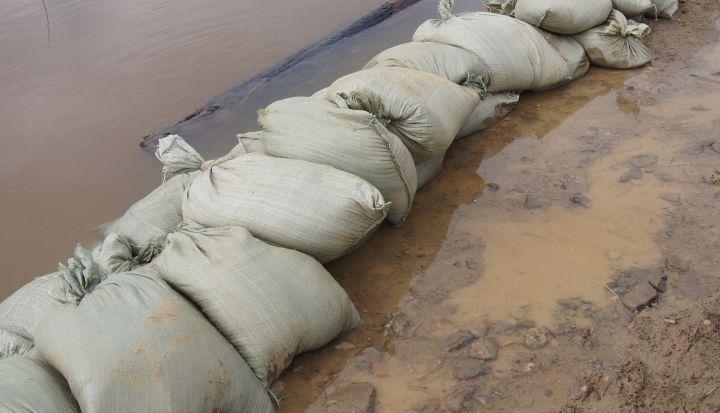 Szare worki wypełnione piaskiem ułożone w zaporę przeciw wlewającej się wodzie