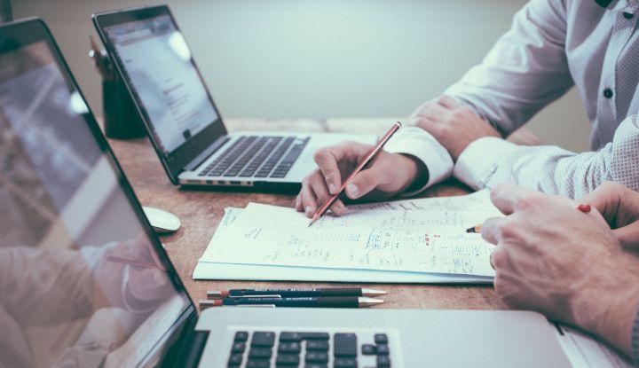 Dwa otwarte laptopy. Męska ręka, która trzyma długipis pokazuje nim coś na lezących na biurku dokumentach