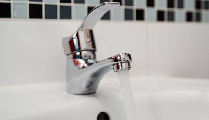 Srebrny kran, z którego leje się woda do umywalki