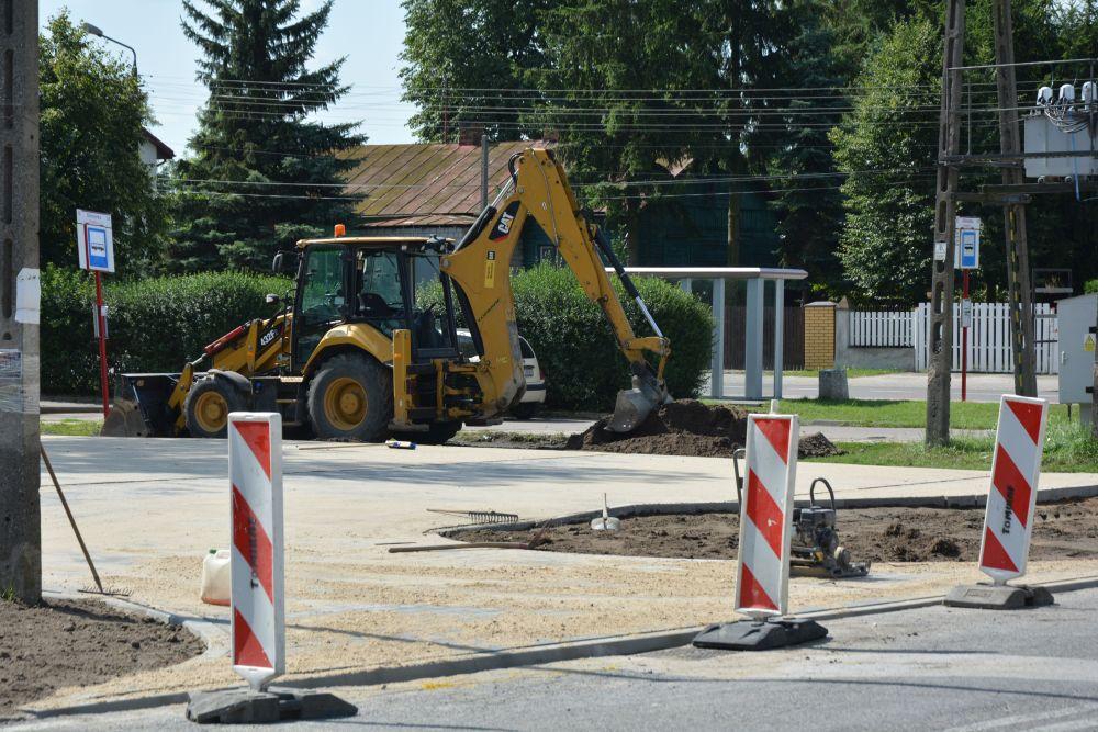 Żółta koparka wyrównuje ziemię przy parkingu w Gliniance