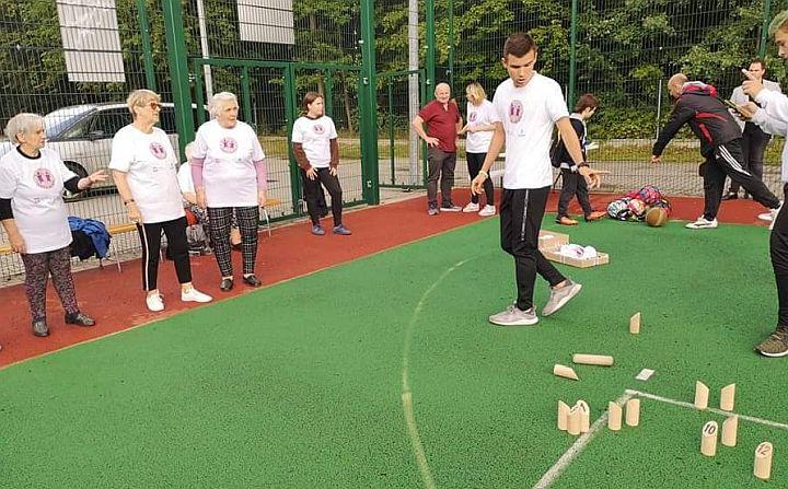 Grupa seniorów z wolonatiuszami grają na boisku