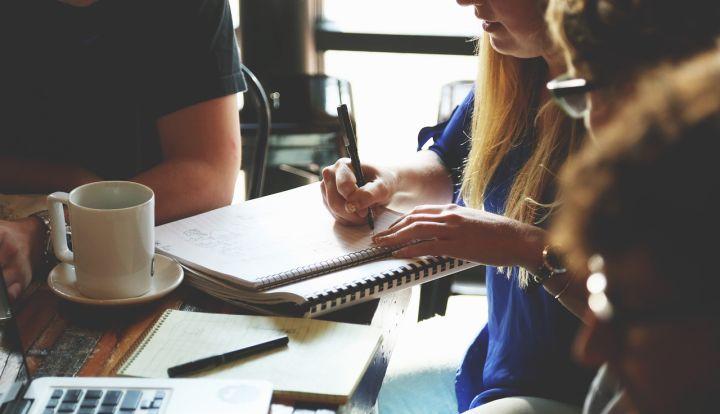 Spotkanie przy stole. Kobieta robi notatki. Na stole widać komputer, notes i biały kubek