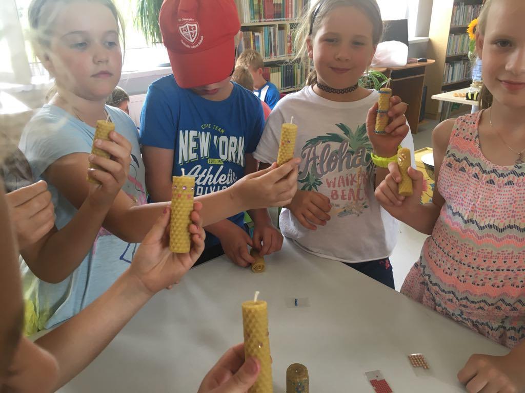Dzieci prezentują świece wykonane z wosku pszczelego