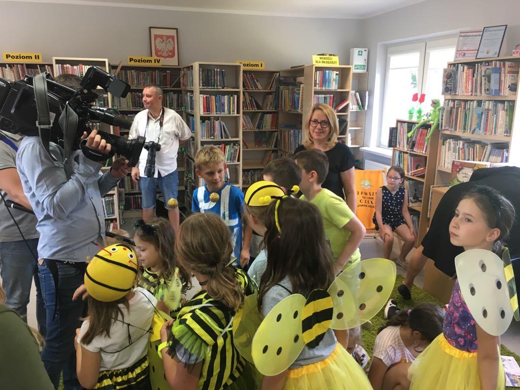 Wnętrze biblioteki w Wiązownie. Na pierwszym planie dzieci przebrane za pszczoły. Z tyłu kamerzysta z TVP