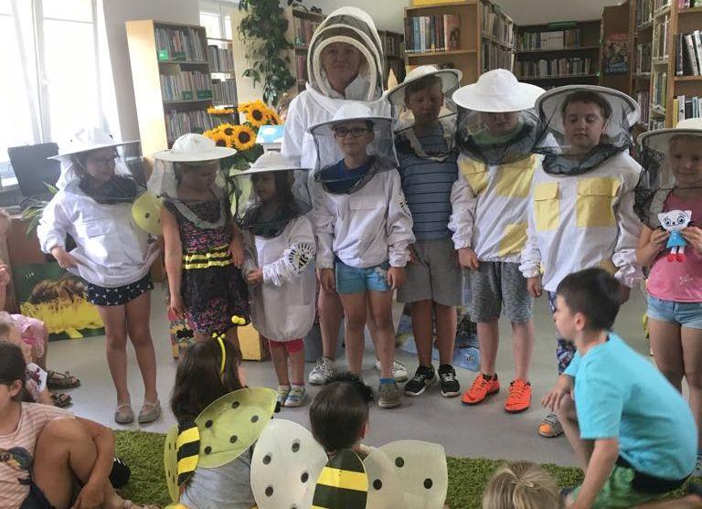 Grupowe zdjecie dzieci i pszczelarki w kapeluszach pszczelarskich