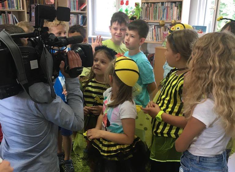 Wnętrze biblioteki w Wiązownie. Na pierwszym planie dzieci przebrane za pszczoły. Z lewej strony kamerzysta TVP
