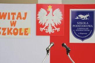 Biało-czerowna flaga, a na niej godło polski po środku, z lewej napis: Witaj w szkole, z prawej - tarcza