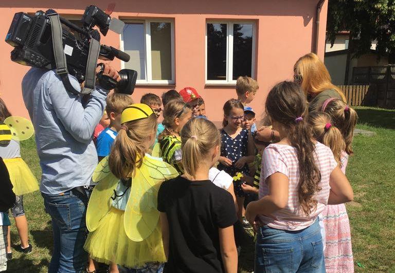 Grupka dzieci na placu przed biblioteką w Wiązownie z lewej strony stoi operator kamery, który filmuje warsztaty z pszczelarstwa