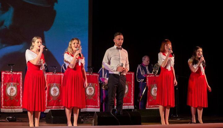 Zespół Dragon podczas występu. Cztery kobiety w czerwonych sukienkach w środku mężczyzna w czarnych spodniach i białej koszuli
