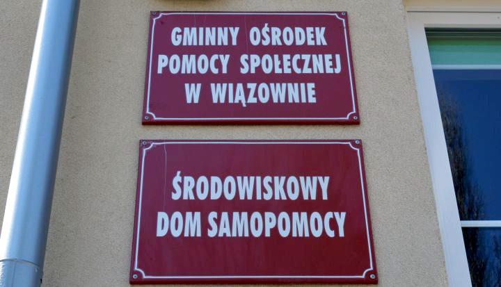 Dwie bordowe tabliczki z napisem Gminny Ośrodek Pomocy Społecznej i Środowiskowy Dom Samopomocy