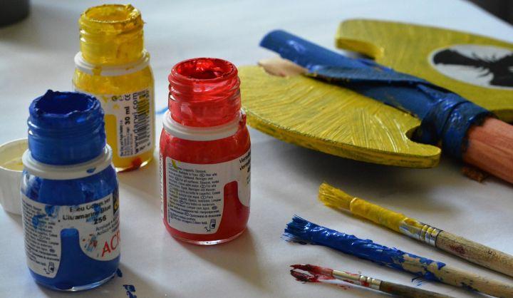 Farby w pojemnikach niebieska, czerwona i żółta. Pędzle i paleta