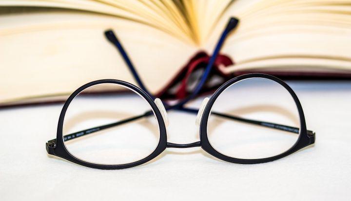 Okulary w czarnych oprawkach do czytania. W tle książka