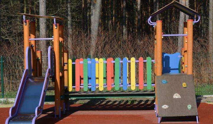 Kolorowe wielofunkcyjne urządzenia na placu zabaw ze zjeżdżalnią, mini ścianką do wspinaczki i mostkiem